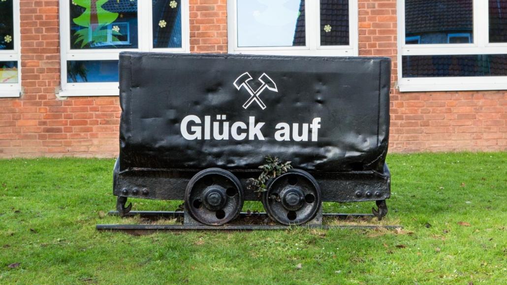 """Eine Lore mit dem Schriftzug """"Glück auf"""" vor der Gemeinschaftsgrundschule Oberwinzerfeld im Ortsteil Winz-Baak"""